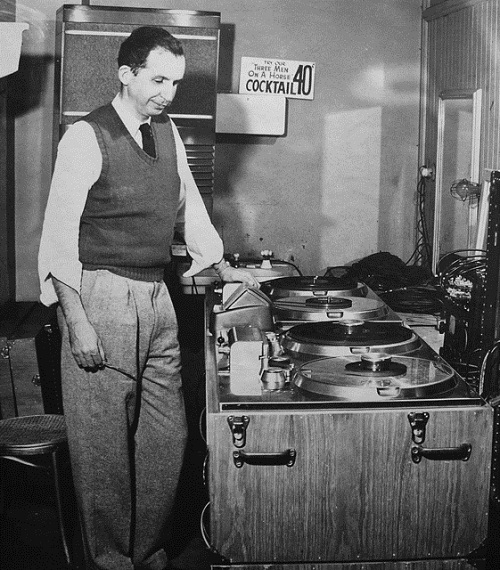 Jack Mullin, scissors in hand, looking over a pair of Ampex model 200s